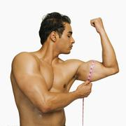 Close-up of a man measuring his biceps with a tape measure Stock Photos