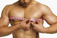 Close-up of a man measuring his chest with a tape measure - stock photo