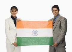 Business executives holding Indian flags - stock photo