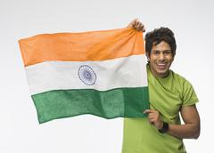 Portrait of a man holding aloft an Indian flag Stock Photos