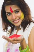 Stock Photo of Portrait of a woman holding Holi colors