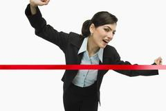 Businesswoman crossing the finishing line - stock photo