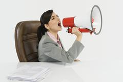 Businesswoman shouting into a megaphone Stock Photos
