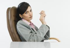 Businesswoman filing her nails in an office - stock photo