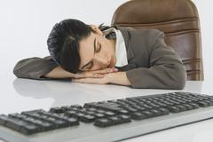 Businesswoman sleeping at desk - stock photo
