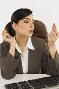 Businesswoman applying nail paint on fingernails in an office - stock photo