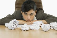 Businesswoman staring crumpled papers on her desk - stock photo