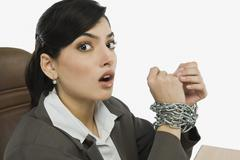 Businesswoman's hands tied up with a chain - stock photo