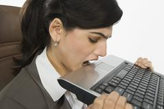 Businesswoman biting a laptop - stock photo
