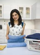 Woman folding laundry - stock photo