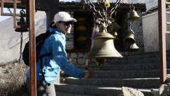 The girl rang the bell at the entrance to a Tibetan monastery Stock Footage
