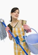 Woman holding a mop and a bucket - stock photo