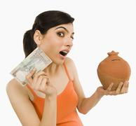 Woman holding Indian currency notes with a piggy bank - stock photo