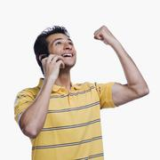 Close-up of a man talking on a mobile phone and clenching fist - stock photo