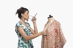 Female fashion designer trying a dress on a mannequin and drinking water Stock Photos