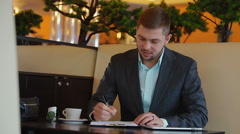 Young, nice businessman sitting at a desk and taking notes in reporting Stock Footage