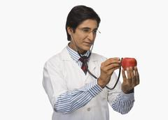 Stock Photo of Doctor listening to an apple with a stethoscope