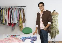 Portrait of a tailor standing in a clothing store and smiling Stock Photos