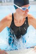 female swimmer exiting pool - stock photo