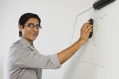 Teacher dusting a whiteboard Stock Photos