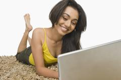 Woman lying on a rug and working on a laptop - stock photo