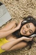 High angle view of a woman lying on a rug and listening to music on headphones Stock Photos