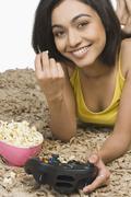 Muotokuva nainen syö popcornia ja pelissä videopeli Kuvituskuvat