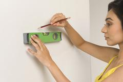 Woman using a spirit level and marking on the wall Stock Photos