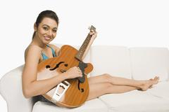 Portrait of a woman sitting on a couch and playing a guitar Stock Photos