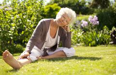 mature woman sitting down on grass comfortably - stock photo