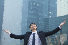 Young businessman smiling and standing outside with arms outstretched Stock Photos