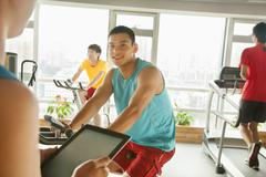 Young man on stationary bike exercising with his personal trainer Stock Photos