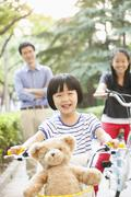 Young Girl Riding Her Bicycle with Her Family - stock photo
