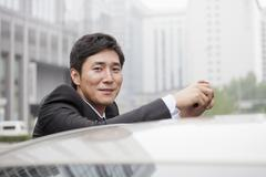 Portrait Of Smiling Businessman Leaning On Car Stock Photos