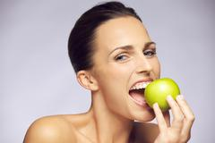young happy woman eating green apple - stock photo