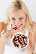 portrait of lovely blonde woman eating cereals with fruit at breakfast - stock photo