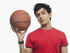 Portrait of a man holding a basket ball Stock Photos