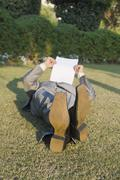 Businessman lying and reading a paper in a park - stock photo