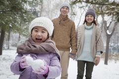 Young girl carrying snow balls in front of parents in park in winter Stock Photos