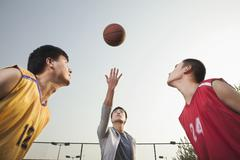 Referee throwing ball in the air, basketball players getting ready for a jump Stock Photos