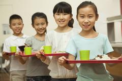 Row of students standing in line in school cafeteria Stock Photos