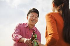 Friends Toasting Each Other on a Rooftop - stock photo