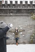 Young man throwing snow balls at young woman on wall Stock Photos