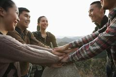 Group of young people smiling and holding hands together on the stone - stock photo
