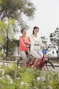 Grandmother and granddaughter riding tandem bicycle, Beijing - stock photo