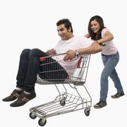 Woman pushing a man sitting in shopping cart - stock photo
