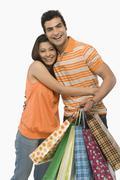 Nainen halaa miestä jolla ostoskassit Kuvituskuvat