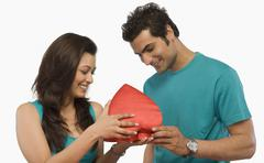 Couple holding a heart shape gift Stock Photos