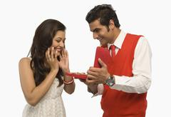 Man giving a gift to his girlfriend - stock photo
