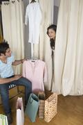 Man looking at a woman peeking out of a fitting room - stock photo